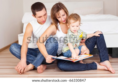 happy family, mother ,father and their baby read a book at home