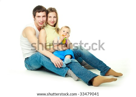 happy family, mother father and their little son sitting on the floor - stock photo