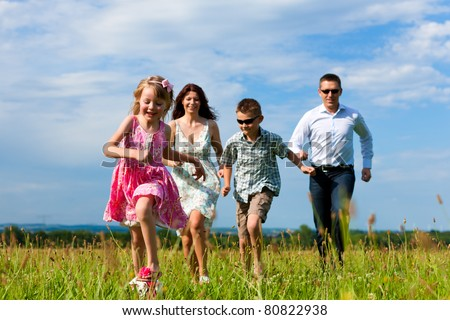 Happy family - mother, father, children - running over a green meadow in summer kicking a soccer ball - stock photo