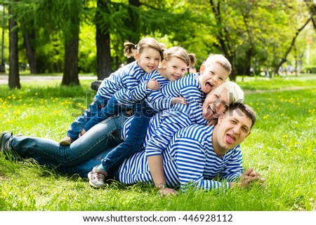 Happy family: mother, father, son and daughters-twins in striped T-shirts having fun in the park on a sunny summer day