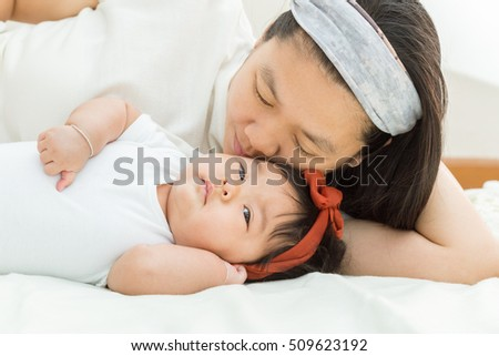 Happy family : Mother holding adorable girl in bedroom.