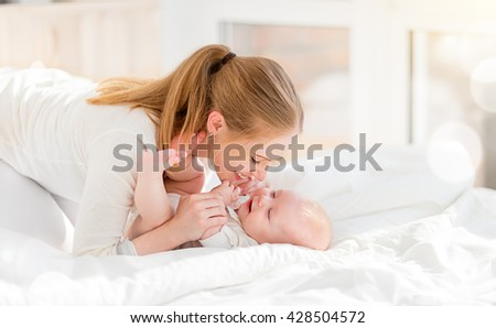 happy family mother in bed with newborn baby - stock photo