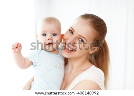 happy family mother playing  with newborn baby - stock photo
