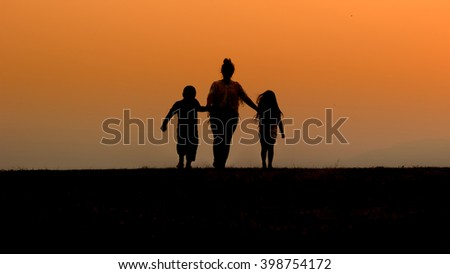 Happy family, mother, son and daughter in nature, sunset