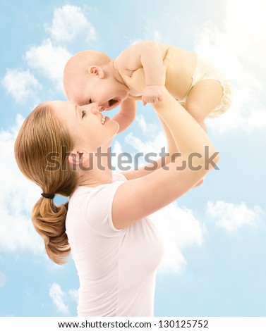 happy family. Mother throws up and kissing baby in the sky in nature - stock photo