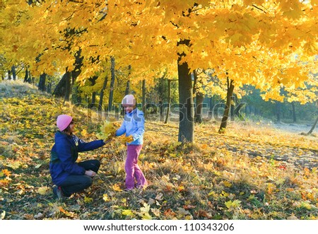 Happy family (mother with daughter) walking in golden maple autumn park - stock photo