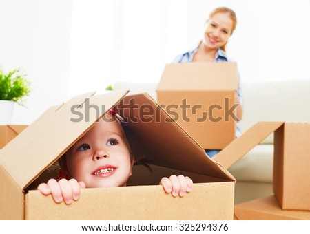 happy family moves into a new apartment. happy baby in a cardboard box - stock photo