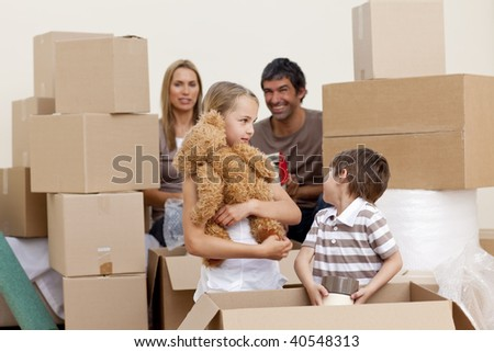 Happy family moving house playing with boxes - stock photo