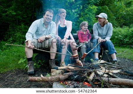Happy family near campfire - stock photo