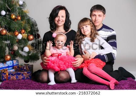 happy family near the Christmas tree. Christmas decor - stock photo
