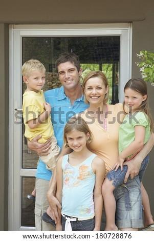 Happy family near their house - stock photo
