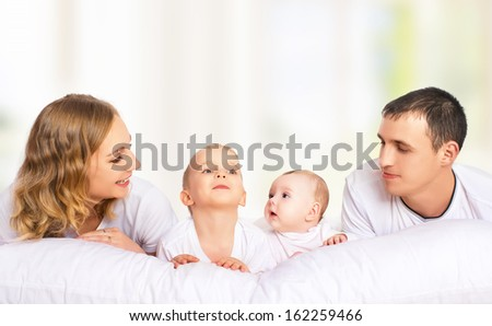 happy family of father, mother and children in bed - stock photo