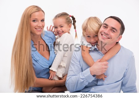Happy family of father mother son and daughter smiling  squatting looking  at camera  isolated on white background waist up