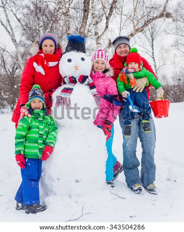 Happy family of five making a snowman