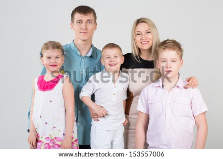 Happy family of five people, mother hugging son in the studio - stock photo