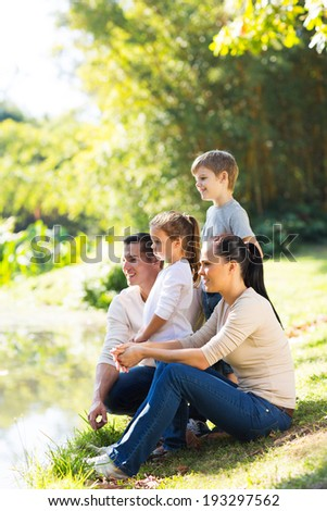 happy family of four by the pond enjoying a day out