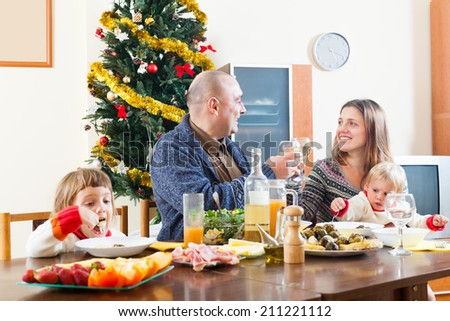 Happy family of four celebrating Christmas over celebratory table