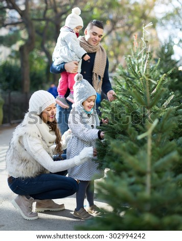 Happy family of four choosing Christmas tree at market. Shallow focus   - stock photo