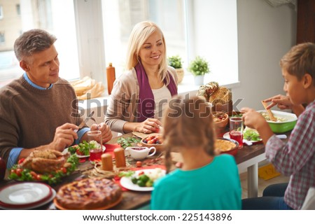 Happy family of four eating traditional Thanksgiving food by the table