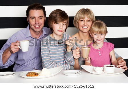 Happy family of four enjoying breakfast at a restaurant. - stock photo