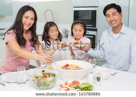 Happy family of four enjoying spaghetti lunch in the kitchen at home