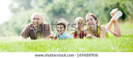 Happy family of four enjoying time at green grass in summer park