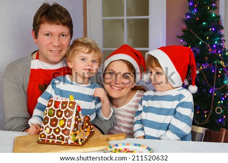Happy family of four: Father, mother and two little sons with self made gingerbread cookie house at christmas time