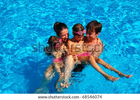 Happy family of four having fun in swimming pool - stock photo