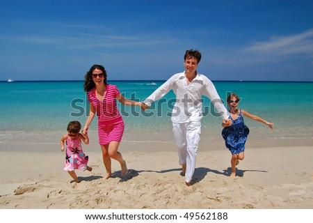 Happy family of four having fun on the beach. Family vacation - stock photo