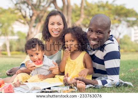 Happy family of four having picnic in the park - stock photo