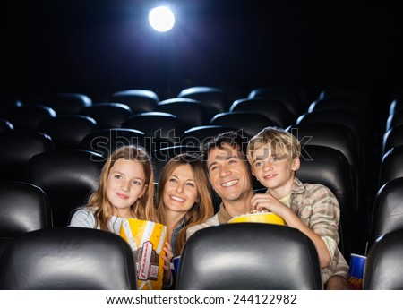 Happy family of four having snacks while watching film in movie theater - stock photo