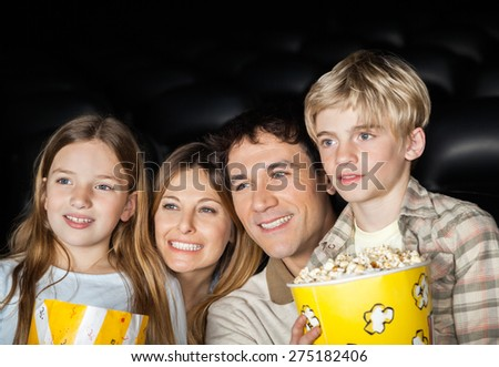 Happy family of four holding popcorn while watching film in movie theater - stock photo