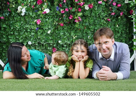 Happy family of four lie on grass near hedge with flowers in garden. - stock photo