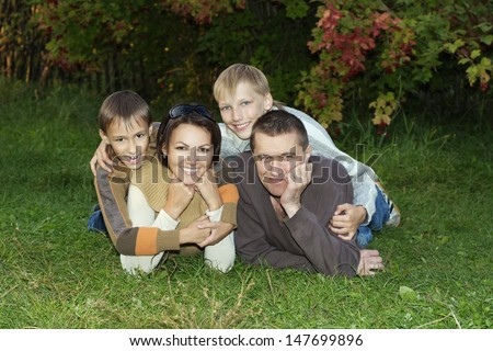 happy family of four lying on the grass in the park