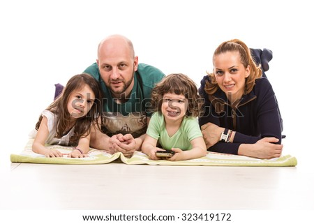 Happy family of four members lying down and smiling to camera - stock photo