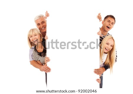 happy family of four peep out through the blank placard isolated on white - stock photo