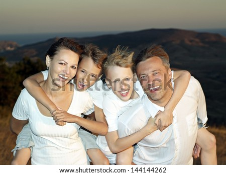 happy family of four people in a landscape together