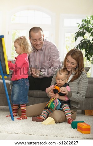 Happy family of four playing in living room smiling.?