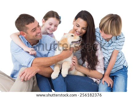 Happy family of four playing with dog over white background - stock photo