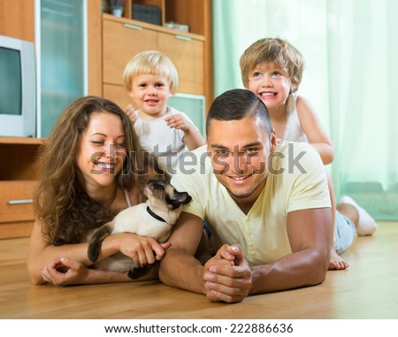 Happy family of four playing with kitten on the floor in living room. Focus on man - stock photo