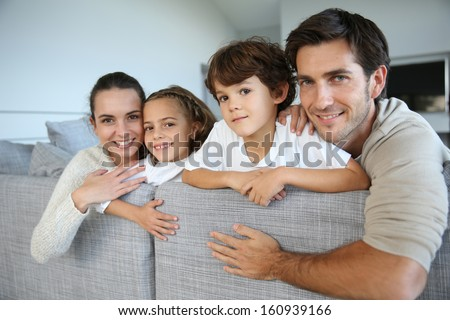 Happy family of four relaxing in sofa - stock photo