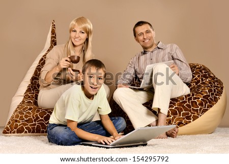 Happy family of four resting at home on beige background - stock photo