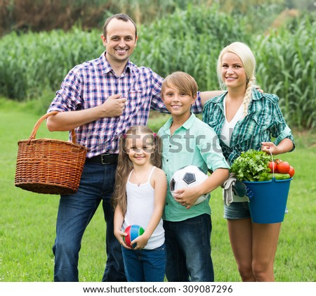 Happy family of four spending summer weekend at countryside