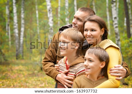Happy family of four standing together in the park in autumn - stock photo