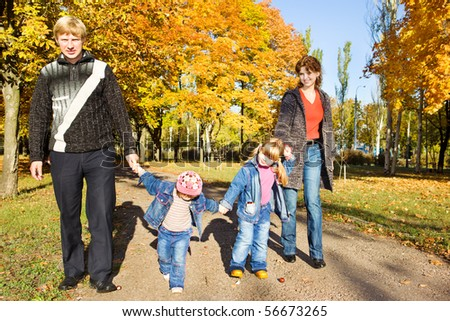 Happy family of four walking in the autumn park