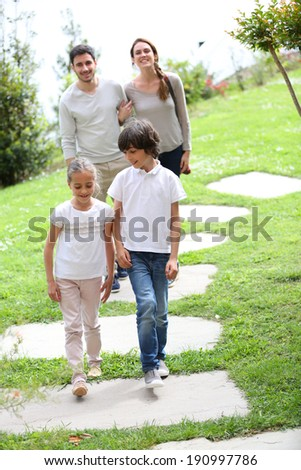 Happy family of four walking towards home - stock photo
