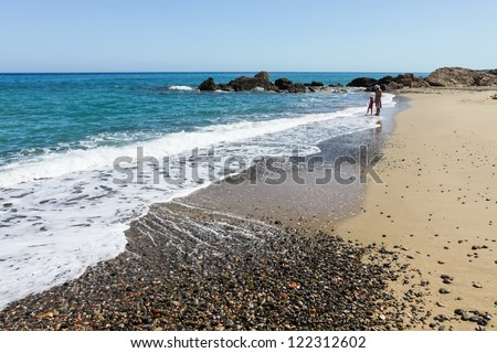 happy family of girl with mother on the sea beach in Spain - stock photo