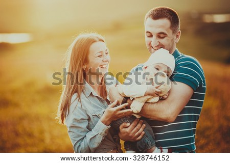 Happy family of mom dad and lovely daughter in sunset light.  - stock photo
