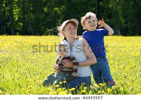 Happy family of mother and two sons in dandelion field