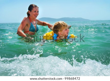 happy family of mother with kid in the waves on the sea beach - stock photo